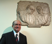 Jim Cavnar, on the Board for Renewal Ministries of Canada, stands in front of the just unveiled wall bas relief of his father, Bobby, and Brian Smith, founders of the Fraternity of Catholic Covenant Communities in their new offices in the Vatican.